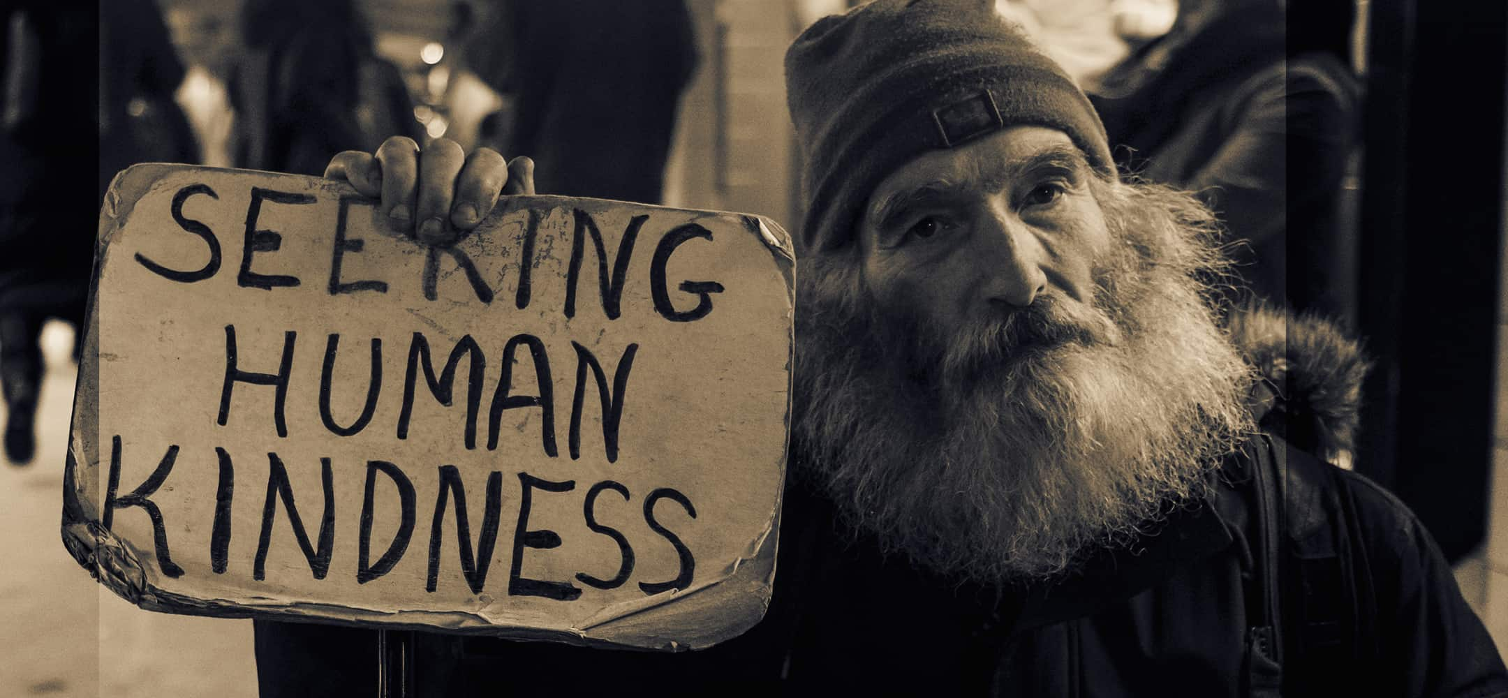 Old Man Holding a Seeking Human Kindness Sign
