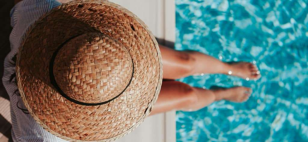 Woman in a Hat Sitting by the Swimming Pool